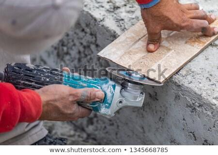 Worker Grinding Corner Tile for Fitting Stock photo © feverpitch