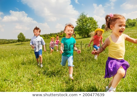 excited running kids in green field play together stock photo © elenabatkova