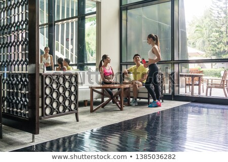 Young people socializing in the lounge area of a trendy health club Stock photo © Kzenon