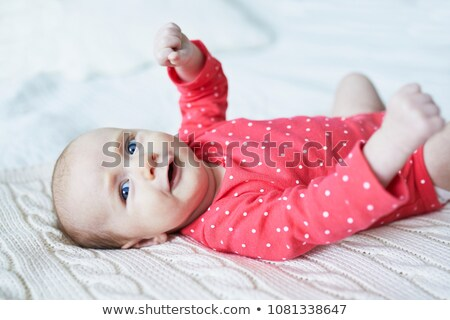 Stock photo: Adorable two months baby girl relaxing in bedroom on knitted blanket on a sunny morning