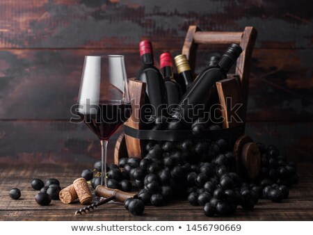 Stok fotoğraf: Elegant Glass Of Red Wine With Dark Grapes And Mini Bottles Of Wine Inside Vintage Wooden Barrel On