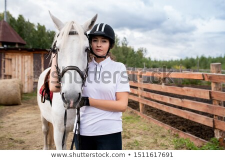 Young sportswoman in activewear standing by white purebred racehorse Stock photo © pressmaster