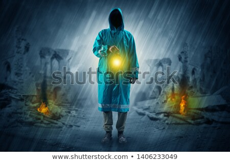 Man with a glowing lantern at a catastrophe scene Stock photo © ra2studio