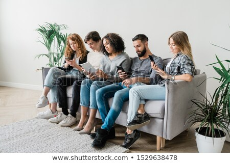 Row of contemporary casual guys and girls in casualwear using modern gadgets Stock photo © pressmaster