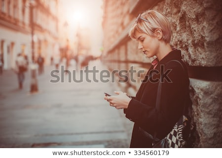 Pretty young woman standing with mobile phone on street at autum Stock photo © boggy