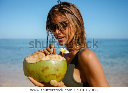 Attractive young woman drinking coconut water on the beach stock photo © galitskaya