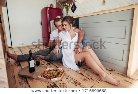 a happy young couple eating pizza at the kitchen stock photo © lopolo