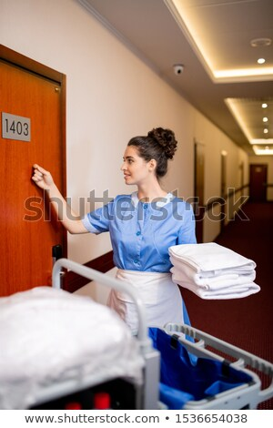 pretty room maid in uniform holding clean towels while knocking on wooden door stock photo © pressmaster