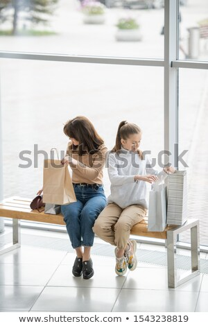 Stockfoto: Young Woman And Her Daughter Sitting On Bench Inside Large Mall