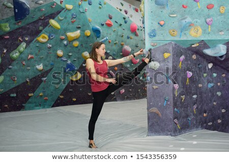 Young sportswoman keeping one leg stretched and raised in front of herself Stock photo © pressmaster