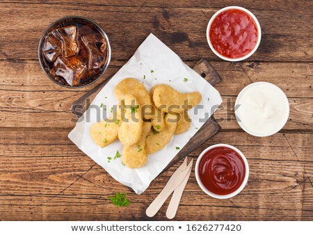 Buttered chicken nuggets on chopping board with glass of cola and ketchup on wooden background.  Stock photo © DenisMArt