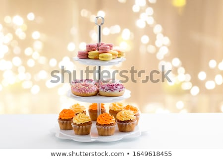 glazed donuts, cupcakes and macarons on stand Stock photo © dolgachov
