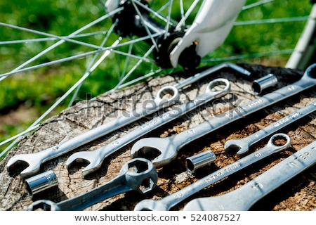 Bicycle repair. Tools, instrument for repairing bike on the wooden stump background with spokes of a Stock photo © Illia
