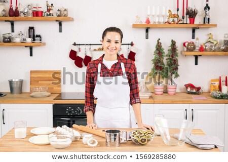 Feliz mulher jovem avental em pé tabela cozinha Foto stock © pressmaster