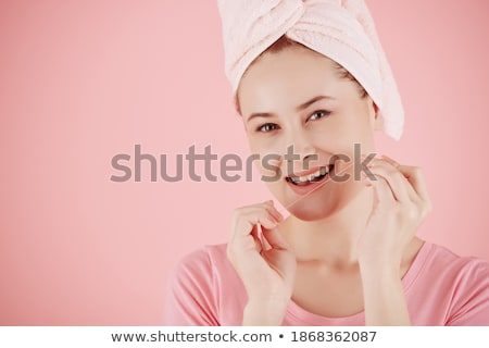 Cheerful healthy young woman with toothy smile using dental floss Stock photo © pressmaster