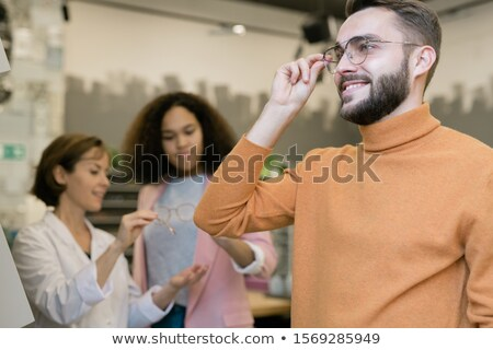 Happy guy trying on pair of eyeglasses on background of consultant and client Stock photo © pressmaster