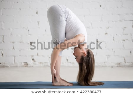 Young woman in activewear stretching legs and bending forwards Stock photo © pressmaster