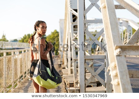 Photo of nice sporty woman using earpods and drinking water Stock photo © deandrobot