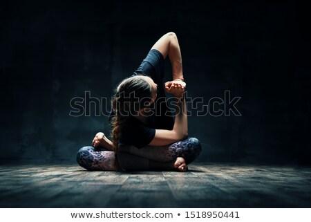 Young woman doing yoga Padmasana pose variation on dark room Stock photo © GVS