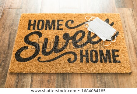 Several Medical Face Mask Rests on Home Sweet Home Welcome Mat A Stock photo © feverpitch
