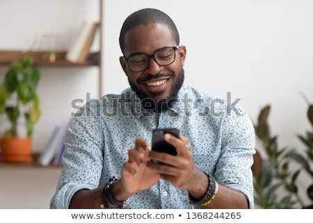 Friendly smiling ethnic businessman on telephone stock photo © lovleah