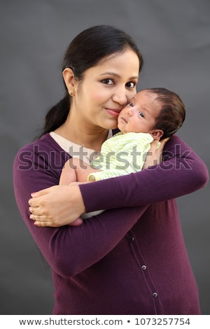 Ethnic Woman Kisses Her Newborn Baby Hand stock photo © feverpitch