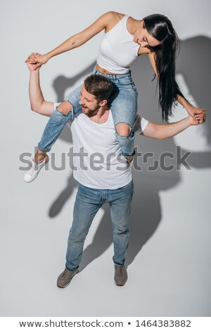 Smiling young couple holding hands eachother while piggyback Stock photo © get4net