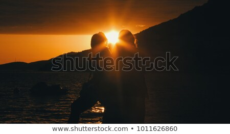 young girl and boy sitting on a rock and watch the sun stock photo © kotenko
