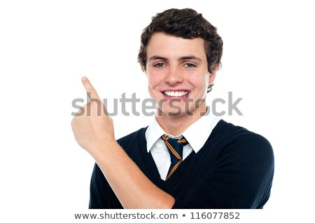 handsome young boy in uniform indicating upwards stock photo © stockyimages