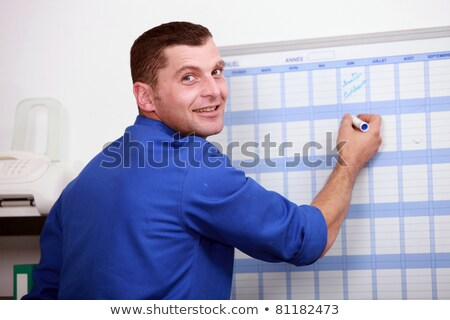 an employee dressed in blue jumpsuite is writing on a calendar Stock photo © photography33