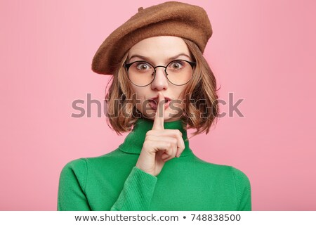 woman showing the sign for silence with her index finger stock photo © imarin