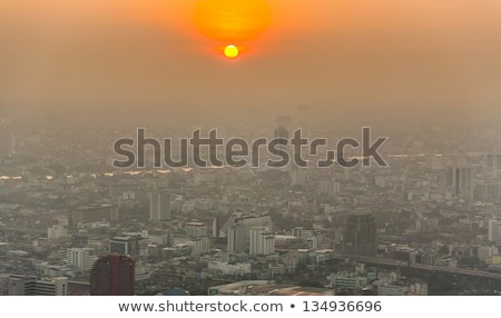 view across bangkok skyline showing in sunset with smog and dust stock photo © meinzahn