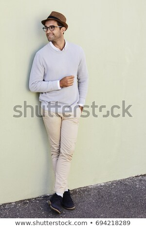 casual man with hat on knee looks away stock photo © feedough