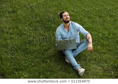 casual man sitting in the grass looking down stock photo © feedough