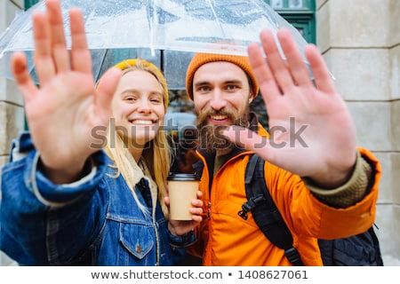 casual man outdoor looks at you with hand on hat stock photo © feedough