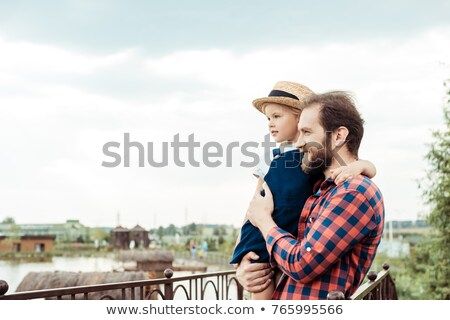 casual man outdoor with hand on hat looks away stock photo © feedough