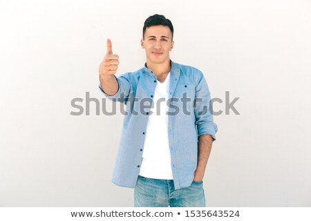 casual man outdoor looks into camera with thumb in pocket Stock photo © feedough