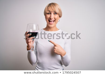 woman in red holding wine glass and smiles stock photo © artjazz