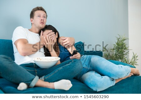 Family Watching Scary Programme On TV Sitting On Sofa Together Stock photo © monkey_business