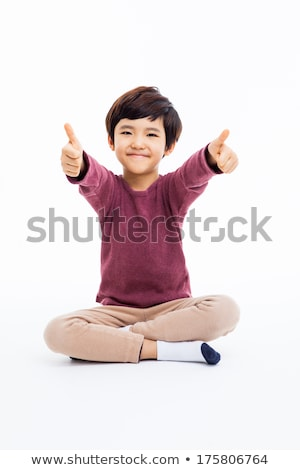 happy asian man sitting on the floor and showing thumb up stock photo © deandrobot