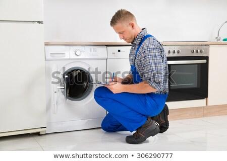 Handyman crouching while writing on clipboard Stock photo © wavebreak_media