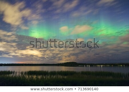northern lights and dark clouds over lake in finland stock photo © juhku