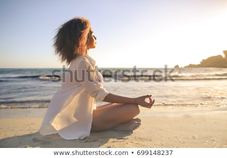 woman doing yoga or meditation outdoors stock photo © godfer