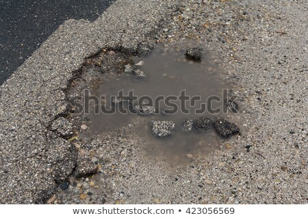 Asphalt road with pothole filled with water and asphalt pieces Stock photo © szabiphotography