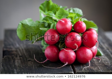 Fresh radishes on old wooden table Stock photo © Yatsenko