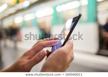 Business people using smartphone at train station. Stock photo © szefei