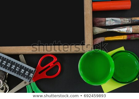 Blank slate with various school supplies on black background Stock photo © wavebreak_media