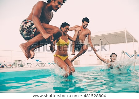 Stock photo: Friends jumping into pool