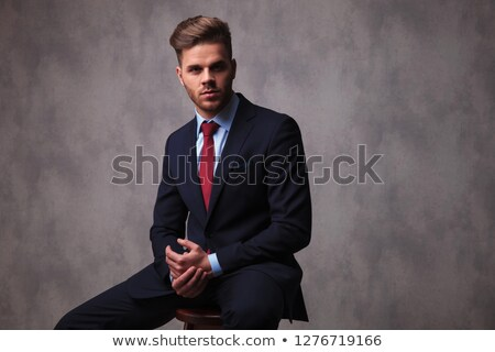 young businessman sits on wooden chair and holds hands together Stock photo © feedough