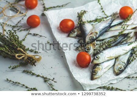 Sardines or baltic herring with tomatoes and rosemary on paper Stock photo © artsvitlyna